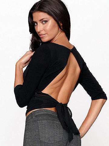 BACKLESS CHIFFON TOP - Flirt your way through the season in this stunning top! Featuring an open back with a sheer chiffon tie, it pairs perfectly with denim for the ultimate day-to-night look. Button closure at the top of the neck. 3/4 length sleeves. Imported.