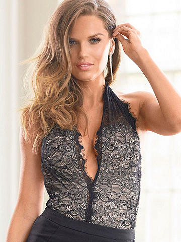 Plunging Lace Bodysuit - With a plunging neckline and crafted from lace, this body suit is nothing short of a sexy essential. Add a pair of strappy heels, a hardside clutch and your favorite denim for a cocktail-hour-ready look. Partially sheer. Deep plunge front. Halter neckline. Nylon/polyester/rayon. Imported.